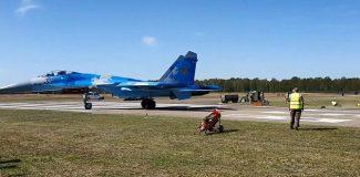 Savaş uçağı, hava gösterisinde pist kenarındaki görevlileri savurdu